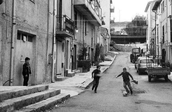 Tre bambini giocano il calcio di strada